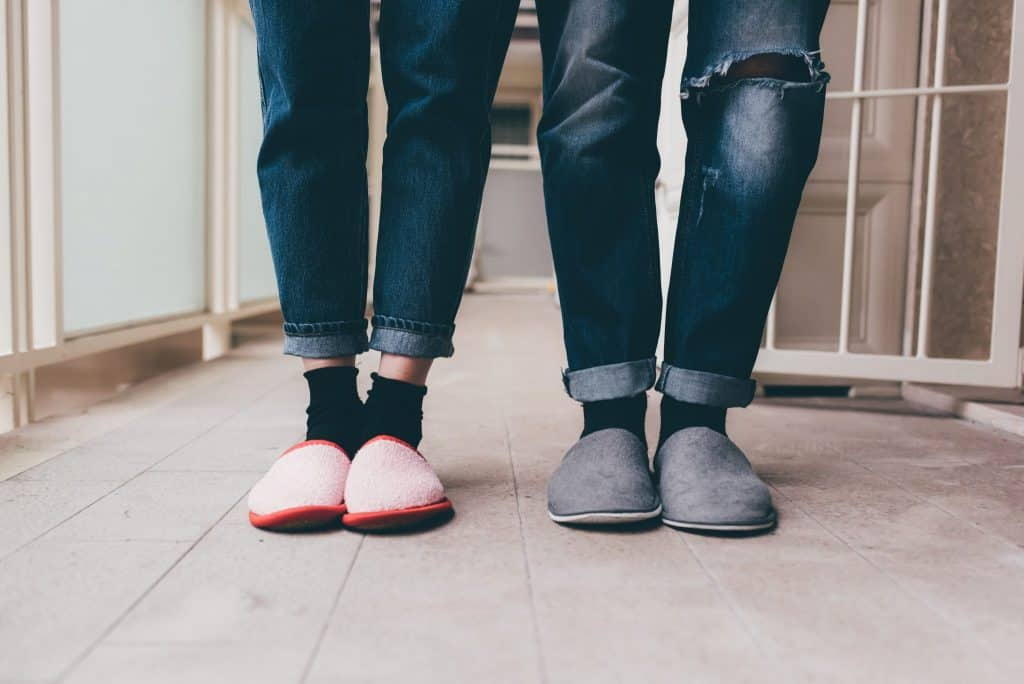 Feet of a couple of young man and woman wearing slippers indoor apartment